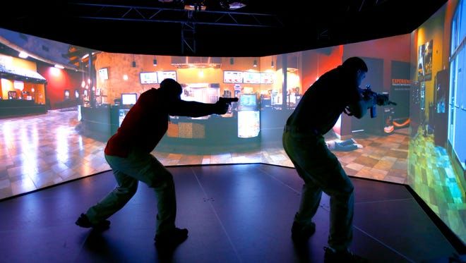 Border Patrol agents take part in training on the VirTra police-shooting simulator at company's headquarters in Tempe on Sept. 17, 2014. The simulator uses commands to de-escalate scenarios to prevent fatal shootings when possible.