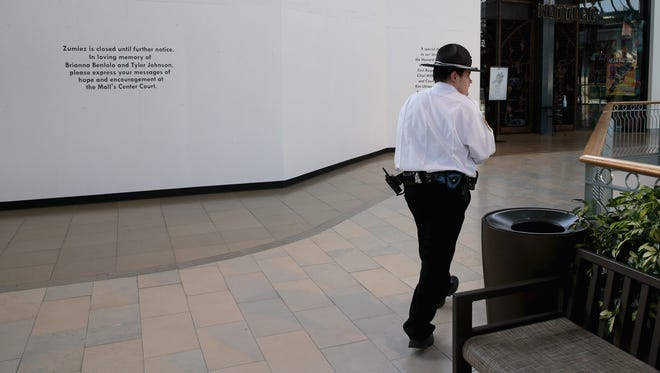 A security guard Jan. 27 walks past the boarded up Zumiez store where two days earlier three people were shot and killed at the Mall in Columbia  in Columbia, Md.