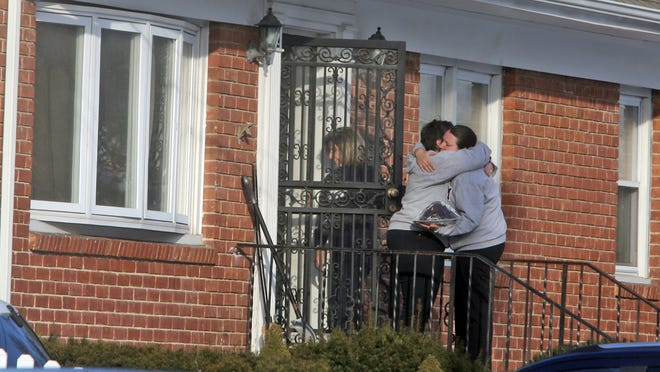 People console each other outside of the home belonging to Barbara DiPietro, on New Haven St. in Harrison. Barbara DiPietro is the mother of Anamarie Hochman, whose husband killed two of their daughters before killing himself yesterday.