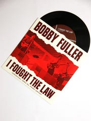 "A copy of the Bobby Fuller 45 rpm record ""I Fought The Law,"" which runs 2:21. The flip side of the record has a song entitled ""A New Shade of Blue,"" which runs 2:57."