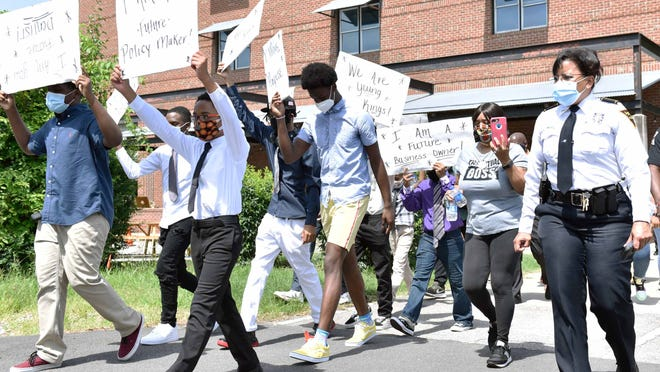Fayetteville Police Chief Gina V. Hawkins marches in the Young Kings March in June in downtown Fayetteville.
