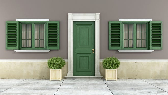 Detail of a classic house with green wooden windows, shutters and front door.