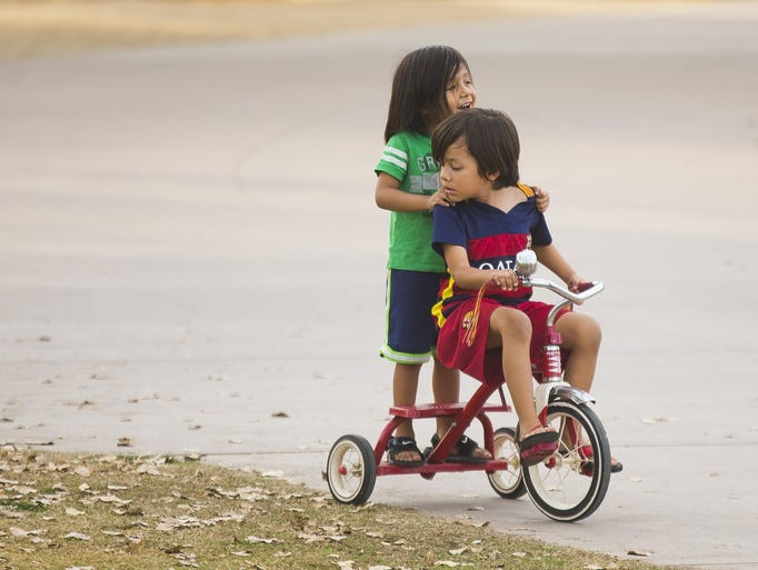 Miguel Cortes rides on the back of the tricycle driven