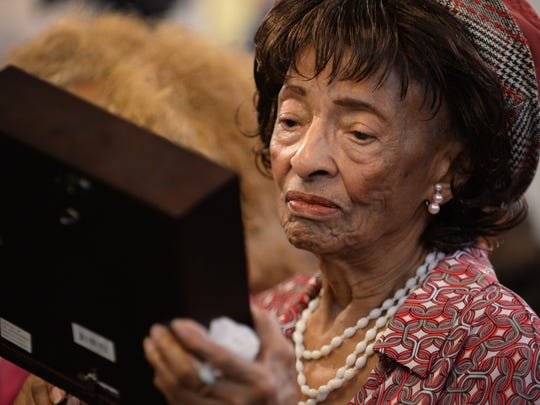 Carolyn Witherspoon, the widow of late World War II vet William Witherspoon,  takes a close look at the framed four service medals given to her husband that he never received.