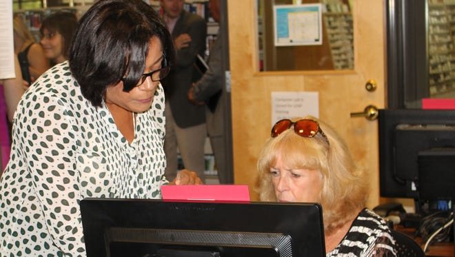 Lolly Cheatham, assistive technology specialist for Advancing Opportunities, assists Carol Yablonowitz of East Brunswick, on the PC in the East Brunswick Public Library's LEAP Training Center.