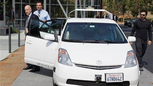 In this file photo, from left, Gov. Jerry Brown, state Senator Alex Padilla and Google co-founder, Sergey Brin arrive at Google headquarters in a driverless car in Mountain View, Calif. For the first time, California's Department of Motor Vehicles knows how many self-driving cars are traveling on the state's public roads. The agency is issuing permits, today that let three companies test 29 vehicles on highways and in neighborhoods.