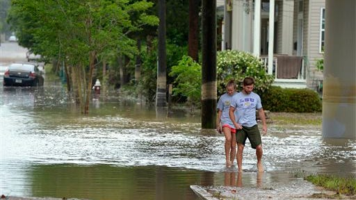 Lindsay Nemanich, left, and Jarett Venn walk through a flooded section of Guillemard Street to check on Venn's car in Pensacola, Fla., Wednesday, April 30, 2014. Heavy rains and flooding have left people stranded in houses and cars in the Florida Panhandle and along the Alabama coast. According to the National Weather Service, an estimated 15-20 inches of rain has fallen in Pensacola in the past 24 hours. (AP Photo/G.M. Andrews)