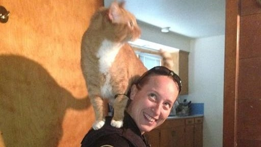A photo provided by the Portland Police Bureau shows Officer Sarah Kerwin with a cat on her shoulder.