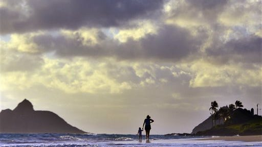 Anne Kllingshirn, of Kailua, Hawaii walks with her daughter Emma, 1, as storm clouds float overhead during the sunrise hours on Kailua Beach, in Kailua, Hawaii, Thursday morning Aug. 7, 2014. The National Weather Service downgraded Hurricane Iselle to a tropical storm about 50 miles before it was expected to make landfall early Friday in the southern part of Hawaii's Big Island. By 2 a.m. Hawaii Standard Time on Friday, the storm was swirling about 10 miles from the Kau coastline. (AP Photo/Luci Pemoni)