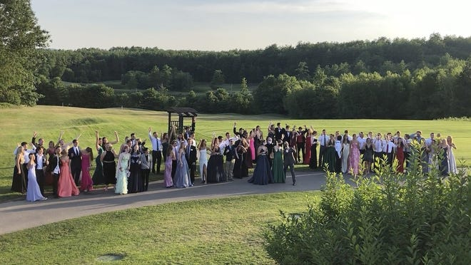 In this July 18 image provided by Carol Justic, recent Bedford High School graduates and students pose for a photo at their outdoor prom outdoor at the Stonebridge Country Club in Goffstown, N.H., organized during the coronavirus pandemic.