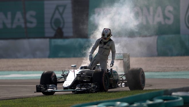 Mercedes driver Lewis Hamilton leaves his car after an engine failure during the Malaysian Formula One Grand Prix at the Sepang International Circuit in Sepang, Malaysia.