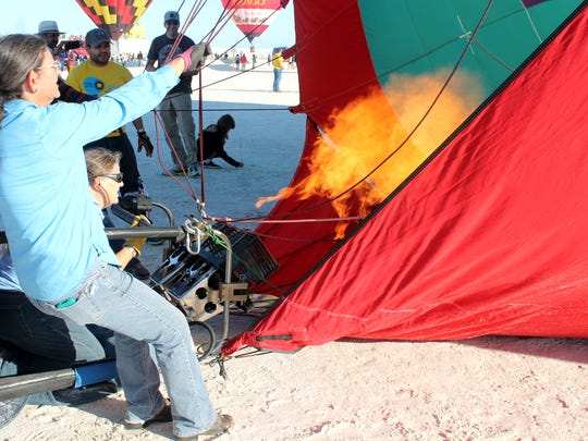 Terry Coley holds the line as pilot Mona Johnson get her balloon, Turquoise Sunrise, ready to launch. Coley, an Alamogordo resident said Turquoise Sunrise is from Tucson, Ariz.