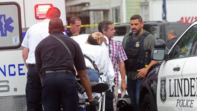 A man fitting the description of Ahmad Khan Rahami, 28, is loaded into an ambulance.