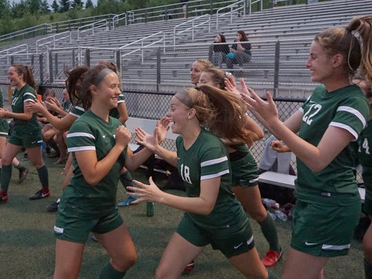Novi players Jenna Daschko (left) Laine Fenchel (18) and Lauren Buchman celebrate their Div. 1 state soccer semifinal victory over Troy advancing to the championship game Friday against Grand Balnc