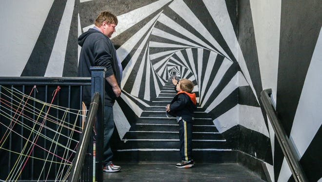 Duane Gaither, left, and Henry Thompson, right, examine a wall mural inside the Murphy Art Center during First Friday, May 5, 2017.