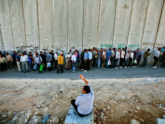 In this 2006 file photo, Palestinian workers stand