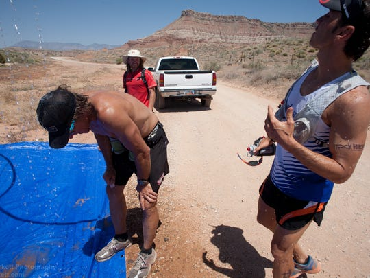Race director Matt Gunn, center, jokes with runners competing in the Zion 100, a 100 mile trail race covering terrain from the town of Virgin up onto Smith's Mesa, to Gooseberry Mesa and back to Virgin, Friday, May 11, 2012.