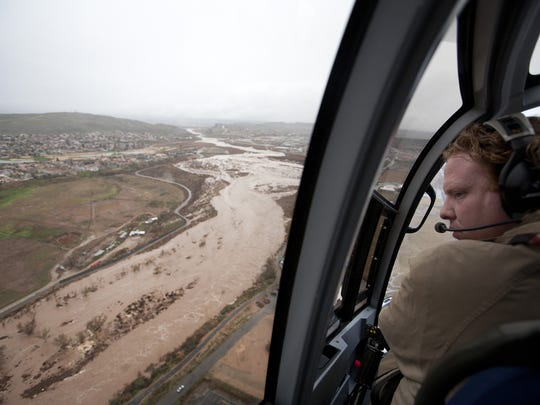 St. George businessman Jeremy Johnson looks out his helicopter over Virgin River flood waters Dec. 21, 2010 during a search and rescue effort.
