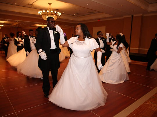 """Debutantes and their escorts dance at the """"Silhouettes of Loveliness"""" Debutante Cotillion."""