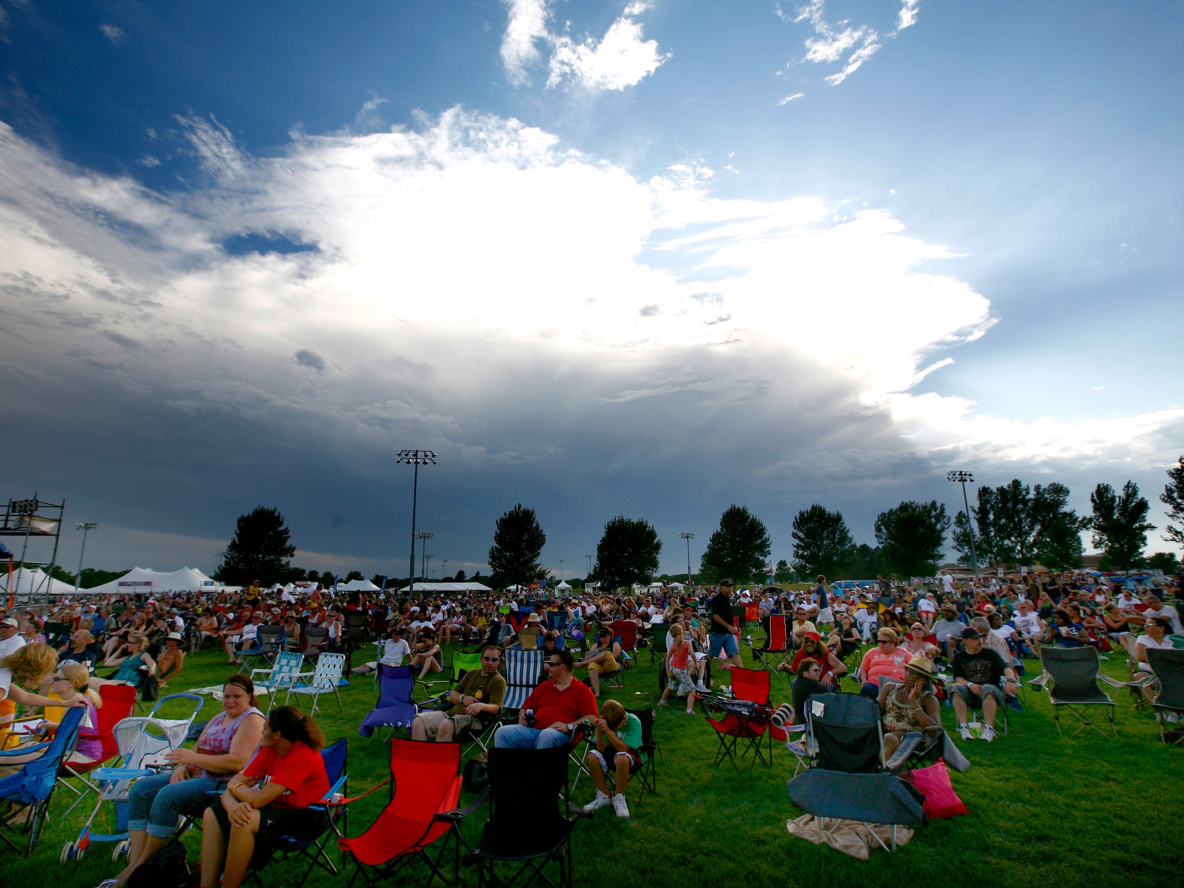 Storm clouds loom on the horizon as JazzFest fans sit on the grass at Yankton Trail Park.