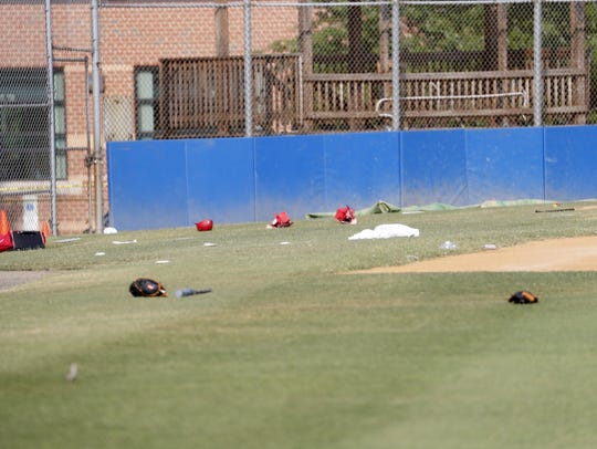 Baseball equipment is seen scattered on the field where