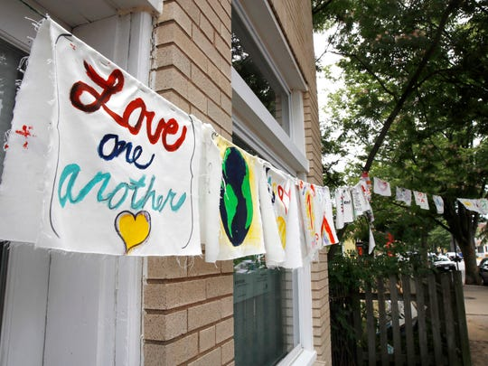"Painted cloth flags including one saying ""Love One Another"" are strung across a store along Mt. Vernon Ave. in Alexandria, Va., Thursday, June 15, 2017, as FBI agents continue to investigate the scene nearby the day after House Majority Whip Steve Scalise of La. was shot during during a congressional baseball practice."
