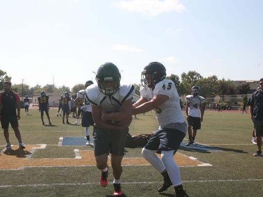 Quarterback Matt Martinez hands the ball off during practice as head coach Brad Mendes watches in the background.