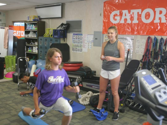 Jeff Shaffer is going through a balance exercise to work on a sprained ankle as student-trainer Holly Ediger looks on.