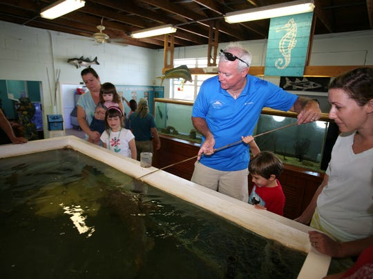 Center teacher Charlie Carr shows visitors at the Open