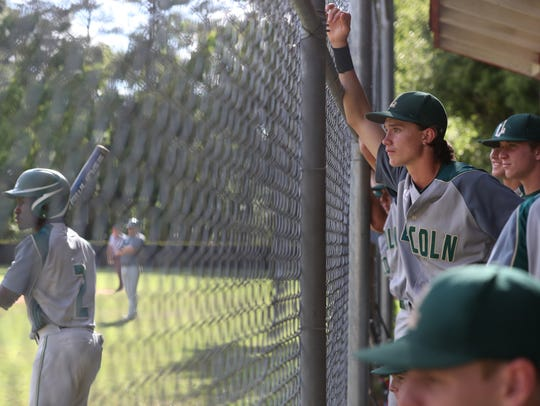 Lincoln players watch from the dugout during their