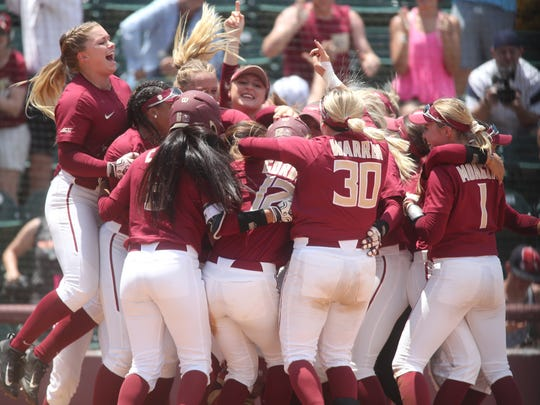 FSU players celebrate Carsyn Gordon's game-winning inside the park home run against Auburn during their NCAA Regional tournament game at JoAnne Graf Field on Saturday, May 19, 2018.