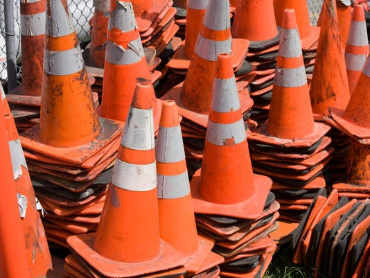 A closeup of used construction cones piled together