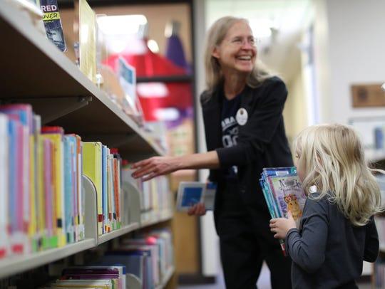 Library Assistant Debra Galloway helps Jessica Reierstad,