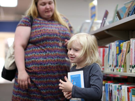 Carolyn Reierstad helps her daughter Jessica, 5, find some reading material at the LeRoy Collins Leon County Public Library downtown on Tuesday.
