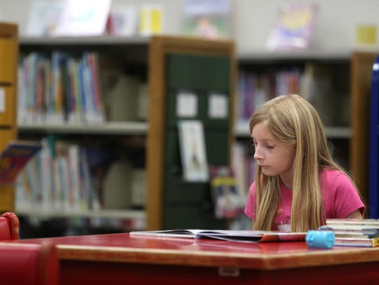 Rebecca Reierstad, 9, reads in the children's section