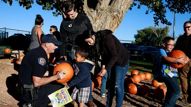 Capt. Taft Tracy, left, hands a signed pumpkin to a child during the Farmington Police Department's National Night Out event on Oct. 4 at the Boys & Girls Clubs of Farmington.