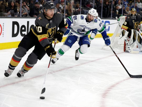 Vegas Golden Knights center Ryan Carpenter (40) skates with the puck as Vancouver Canucks center Sam Gagner (89) defends during the second period of an NHL hockey game Friday, Feb. 23, 2018, in Las Vegas. (AP Photo/Isaac Brekken)