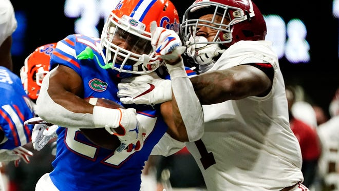 Florida running back Dameon Pierce goes into the end zone for a touchdown Saturday against Alabama linebacker Ben Davis during the second half of the SEC Championship Game in Atlanta.