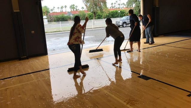 Volunteers mop water off of the gym floor at Desert Chapel Christian High School after a rain and wind storm that hit Palm Springs on September 9, 2017.