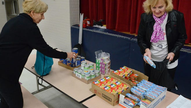 Huron Valley Optimists Bev Orndorf, left, and Diana Mahacek were among the dozens of good people who showed up to White Lake's Brooks Elementary on Oct. 14 to kick off the Blessings in a Backpack food donation program within the schools.