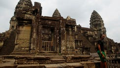A tourist stands at Angkor Wat in Siem Reap, Cambodia,
