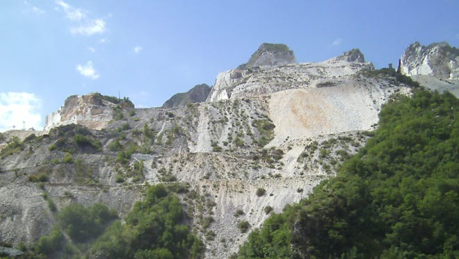 Snow-covered peaks? No, it's the white exposed Carrara marble in quarries.