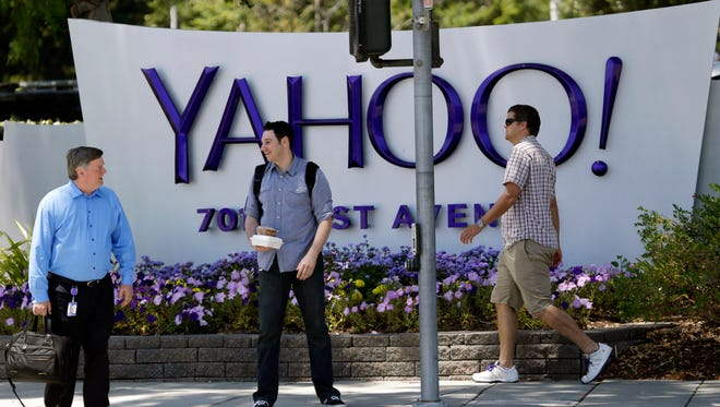 In this June 5, 2014, file photo, people walk in front of a Yahoo sign at the company's headquarters in Sunnyvale, Calif.