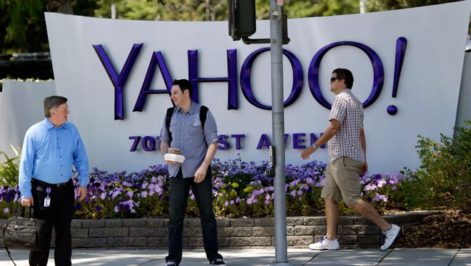 """FILE - In this June 5, 2014, file photo, people walk in front of a Yahoo sign at the company's headquarters in Sunnyvale, Calif. Yahoo says the personal information of 500 million accounts have been stolen in a massive security breakdown that represents the latest setback for the beleaguered internet company. The breach disclosed on Thursday, Sept. 22, 2016, dates back to late 2014. Yahoo is blaming the hack on a """"state-sponsored actor."""" (AP Photo/Marcio Jose Sanchez, File)"""