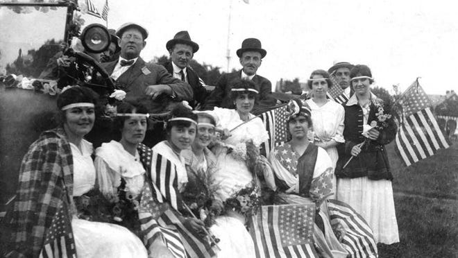 """In August 1916, French-Canadian workers crafted a prize-winning float in the second annual parade and field day of the American Woolen Company in Winooski. Miss Alfreda Fisher dressed as """"Liberty (seated with flag wrapped around her head), and her escorts, earned second place."""
