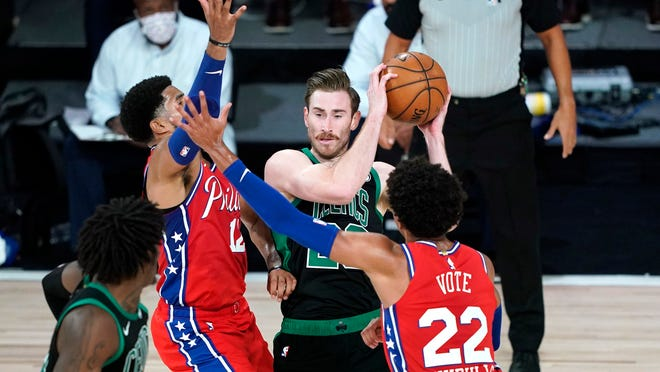 Boston Celtics' Gordon Hayward, center looks to pass as Philadelphia 76ers' Matisse Thybulle (22) and Tobias Harris (12) defend during the first half of an NBA basketball first round playoff game Monday, Aug. 17, 2020, in Lake Buena Vista, Fla.