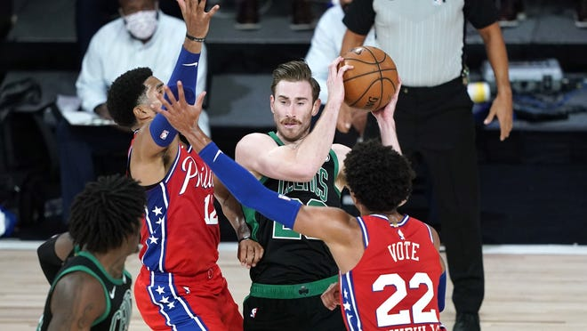 The Boston Celtics' Gordon Hayward, center looks to pass as Philadelphia 76ers' Matisse Thybulle (22) and Tobias Harris (12) defend during the first half of their first round playoff game, last Monday, Aug. 17, in Lake Buena Vista, Fla.