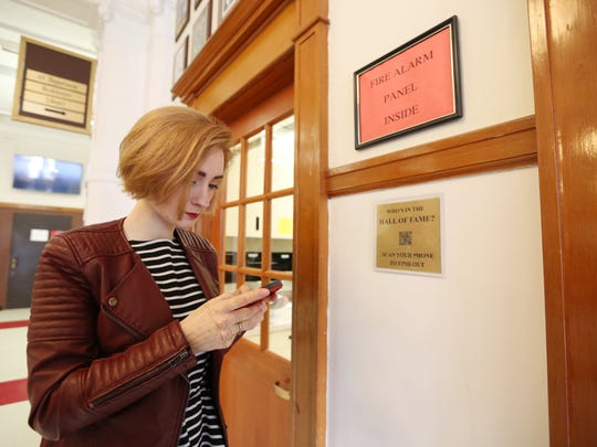 Junior Elliana Chidwick shows how to scan QR codes to view more information about the North Salem High School Hall of Fame members on Wednesday, March 1, 2017. The Hall of Fame is on display at the main entrance of the school and features a variety of notable alumni, including senators, actors, artists and professional athletes, among others.