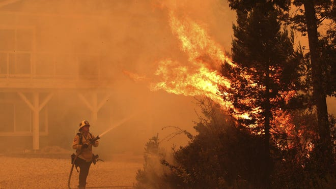 Firefighter David Widaman directs water onto a tree that had exploded in flame as a fire crew defends a house northwest of Santa Cruz, Calif., Wednesday Aug. 19, 2020.