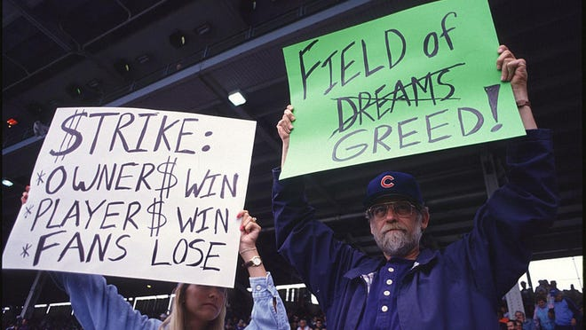 Fans hold up signs in protest of the baseball strike on Aug. 10, 1994, during a game between the San Francisco Giants and the Chicago Cubs at Wrigley Field. Very little has actually happened since then to solve the game's problems.